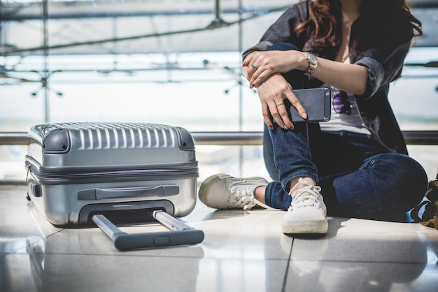 Cerca de la mujer joven con maleta de bolsa y maleta esperando para la salida Foto Premium