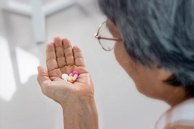 Cerca de mujer senior con pastillas y vaso de agua en casa, tomar medicamentos. Foto Premium