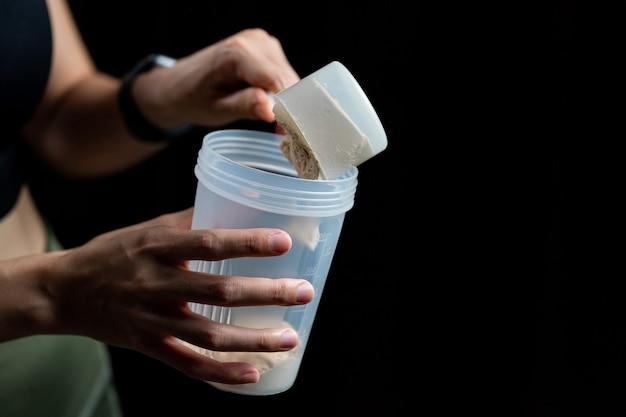 Cerca de mujeres con cucharada de medición de proteína de suero y botella agitadora, preparando batido de proteínas. Foto Premium