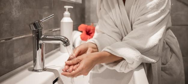 Cerca de una niña en bata de baño se lava las manos en el baño. Foto gratis