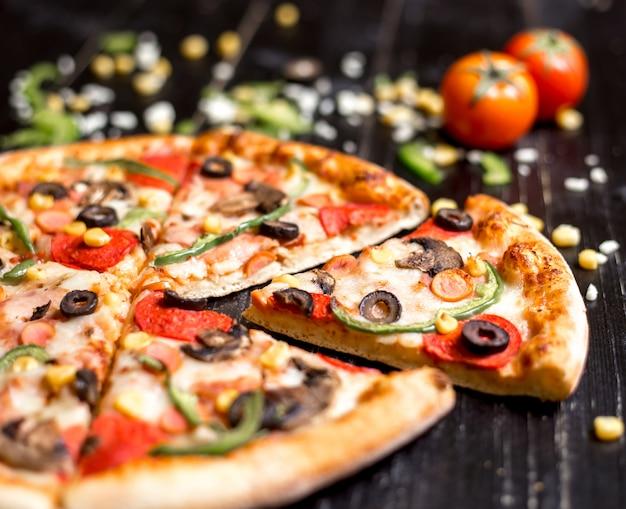Cerca de rebanadas de pizza de pepperoni con salchichas champiñones oliva pimiento y queso Foto gratis
