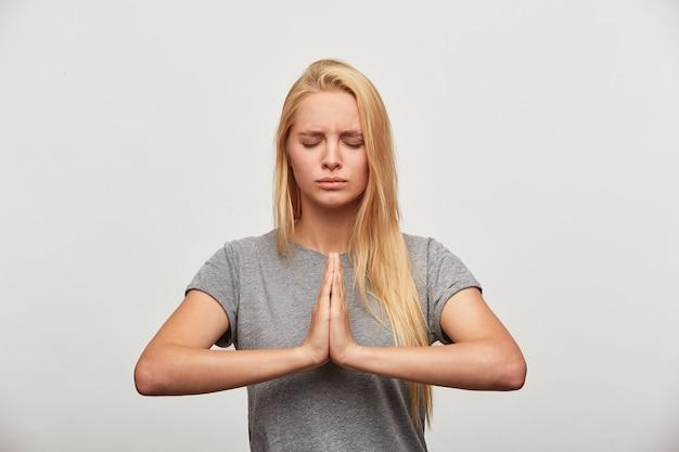 Cerca de rubia meditando, se concentra en algo, practicando ejercicios de yoga de respiración Foto gratis