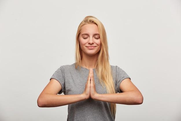 Cerca de la tranquila mujer rubia sonrisas, se concentra en algo agradable, practicando ejercicios de yoga de respiración Foto gratis
