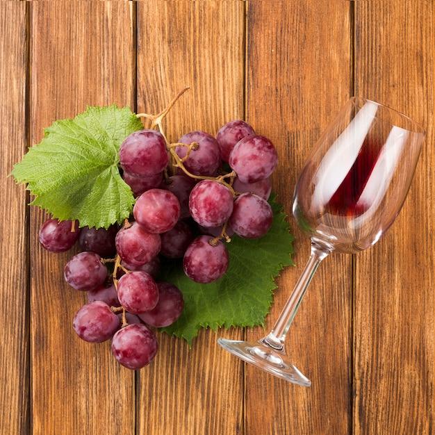 Cerca de uvas y copa de vino tinto Foto gratis
