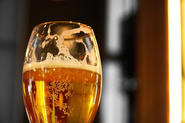 De cerca en un vaso de pinta de cerveza ámbar pale ale, proyectando una sombra sobre una mesa de madera Foto Premium