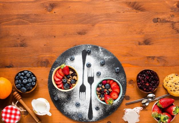 Cereal. desayuno con muesli y frutas frescas en tazones sobre una mesa de madera rústica Foto Premium
