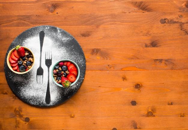 Cereal. desayuno con muesli y frutas frescas en tazones sobre una superficie de madera rústica, Foto Premium