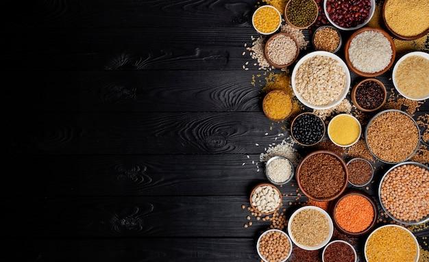 Cereales, granos, semillas y granos fondo negro de madera Foto Premium