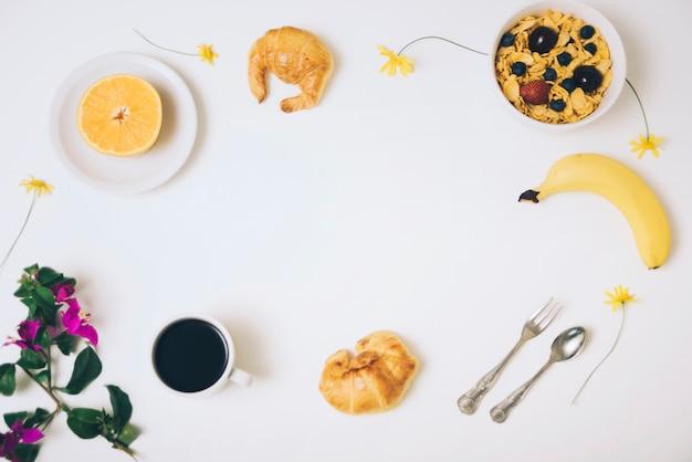 Cereales de maíz; plátano; croissants copa de naranja y café a la mitad con flor de buganvilla sobre fondo blanco Foto gratis