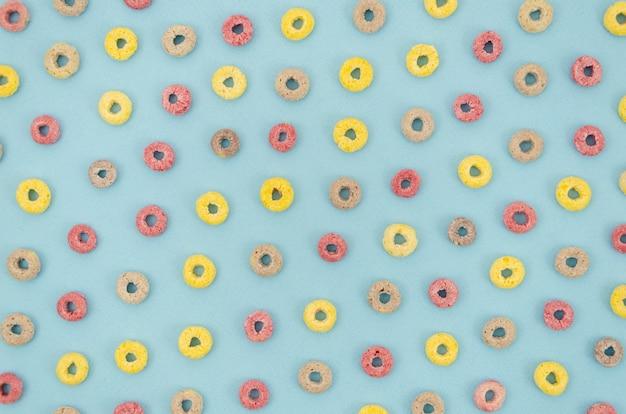 Cereales multicolores con sabor a fruta sobre fondo azul. Foto gratis