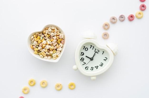 Cereales y reloj sobre fondo blanco. Foto gratis