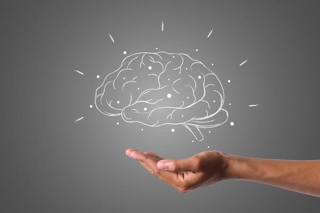 El cerebro escribe con tiza blanca está a la mano, dibuja el concepto. Foto gratis