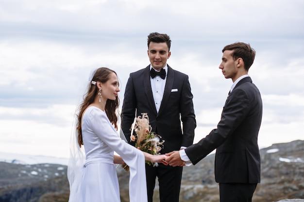 Ceremonia de salida en la cima de la montaña, el novio sujeta la mano de la novia contra el fondo del maestro de ceremonias. Foto Premium