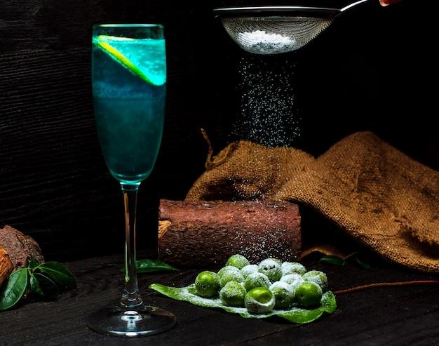 Cereza ciruela espolvoreada con sal y un vaso de bebida fría Foto gratis