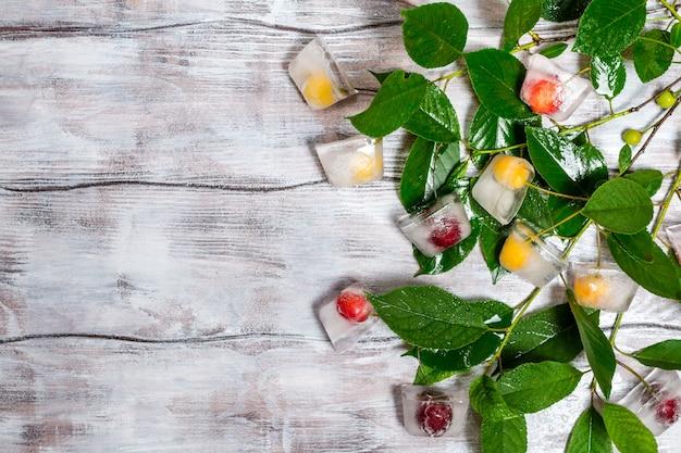 Cereza en cubo de hielo con rama en textura de madera pintada de blanco como vista superior de fondo Foto Premium