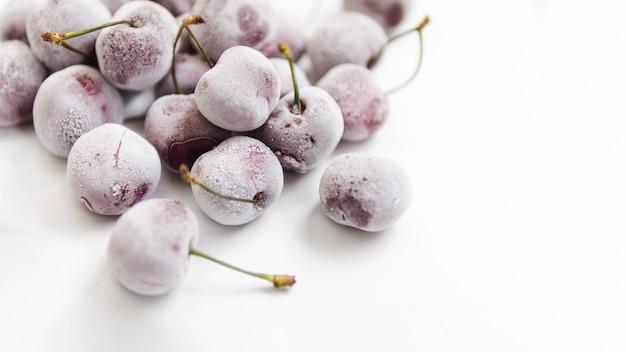 Cerezas congeladas sobre fondo blanco Foto gratis