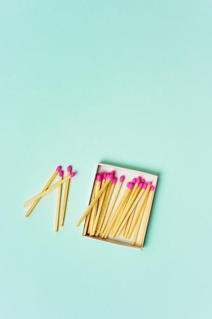 Cerillas de madera brillantes dispersas de la caja de cerillas sobre un fondo de color pastel turquesa Foto Premium