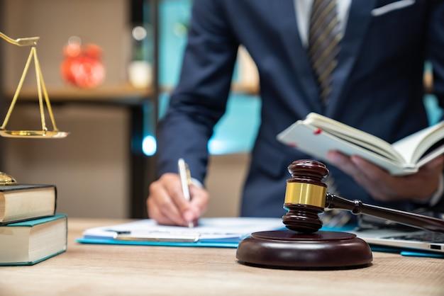Cerrar abogado empresario trabajando o leyendo el libro de leyes en el lugar de trabajo de oficina para el concepto de abogado consultor Foto Premium