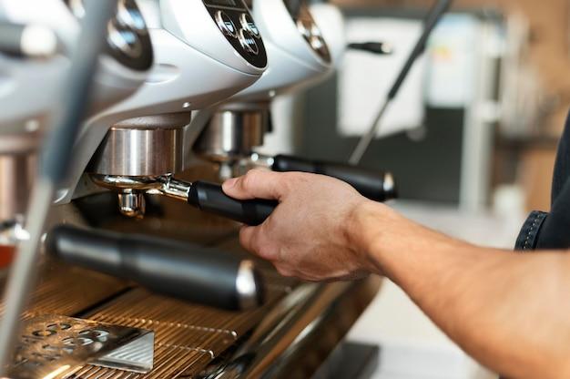 Cerrar barista con máquina de café Foto gratis