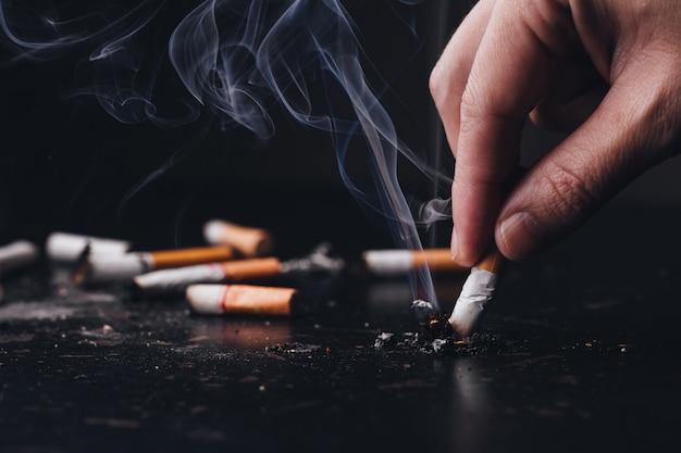 Cerrar un cigarrillo de mano para aplastar el humo de un ardor, dejar de fumar. día mundial sin tabaco Foto Premium