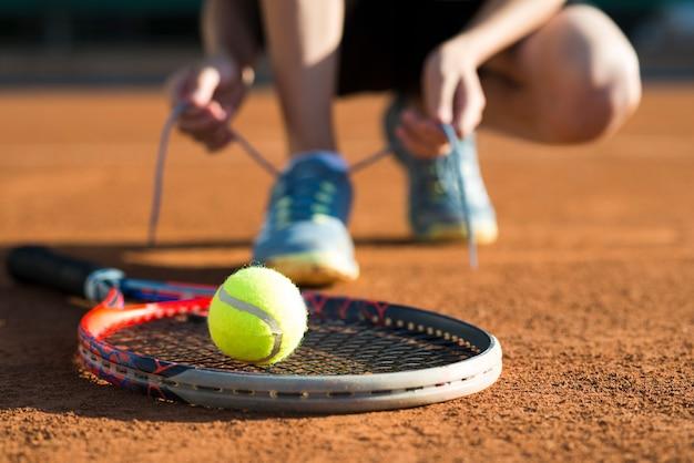Cerrar el cohete de tenis con la pelota en él Foto Premium