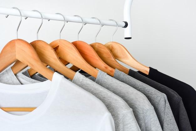 Cerrar colección de camisetas negras, grises y blancas colgadas en perchas de madera Foto Premium
