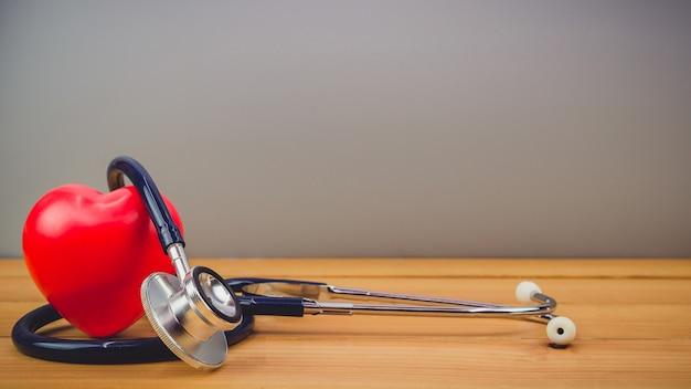 Cerrar corazón rojo y un steythoscope en mesa de madera vieja Foto Premium