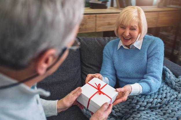 Cerrar y cortar vista del viejo hombre dando un regalo a la esposa hai. Foto Premium