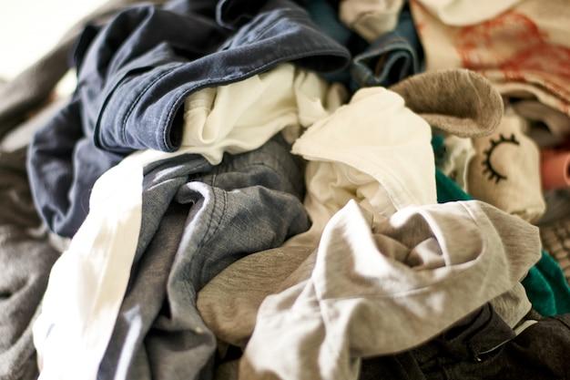 Cerrar en una gran pila de ropa y accesorios tirados al suelo Foto Premium