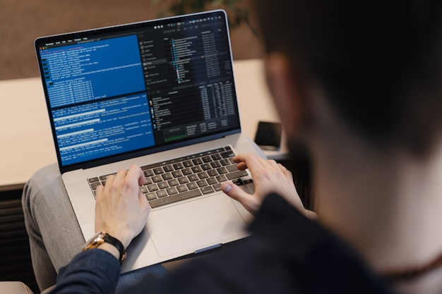 Cerrar hombre escribiendo código en la computadora portátil Foto gratis