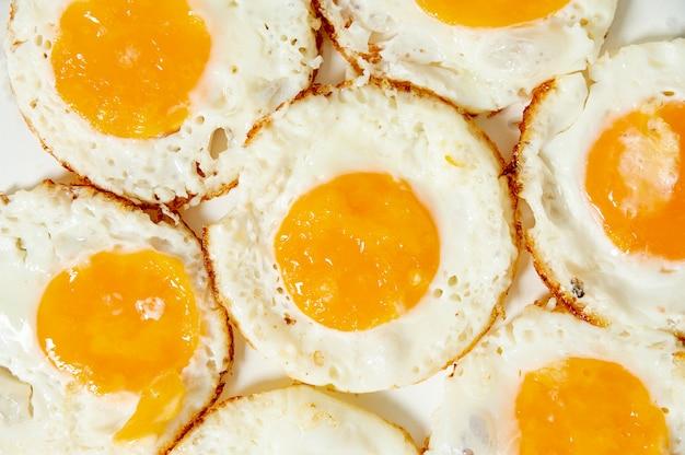 Cerrar huevos fritos sobre fondo liso Foto gratis