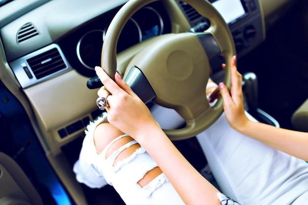 Cerrar imagen de estilo de vida de mujer elegante conduciendo su coche, manicura perfecta y accesorio, pantalones locos de mezclilla vintage, concepto de carretera de viaje. Foto gratis