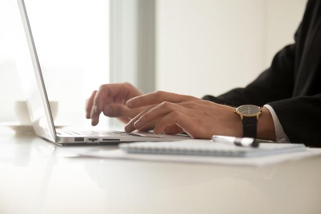 Cerrar imagen de mans manos en reloj de pulsera escribiendo en la computadora portátil Foto gratis