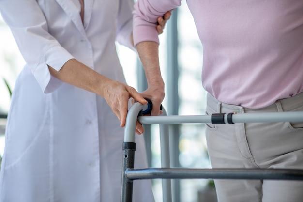 Cerrar imagen de una mujer con andador y un médico Foto Premium
