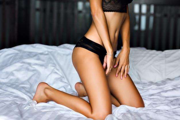 Cerrar imagen de mujer sexy posando en la cama, cuerpo bronceado delgado, lencería negra, disfruta de su mañana, estilo de vida de lujo. Foto gratis