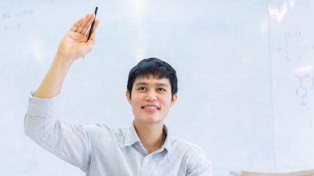 Cerrar joven asiático estudiante universitario hombre levantar la mano para preguntar al maestro sobre proyecto o examen en el aula para la educación y el concepto de personas Foto Premium