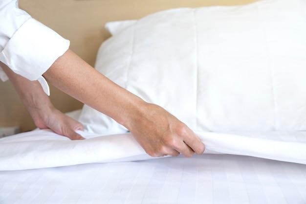Cerrar mano configurar sábana blanca en habitación de hotel Foto Premium