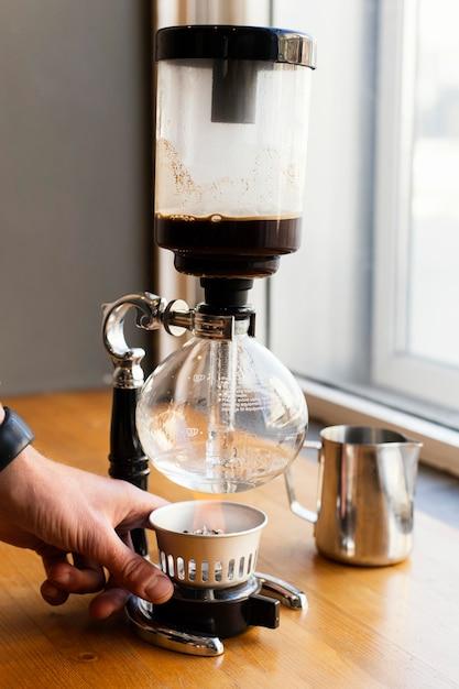 Cerrar mano con máquina de café Foto gratis