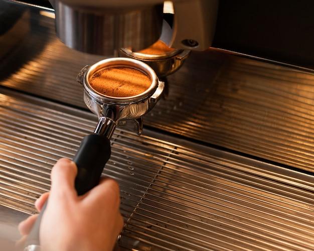 Cerrar mano preparando café con máquina Foto gratis