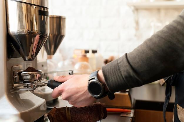 Cerrar mano con reloj preparando café Foto gratis
