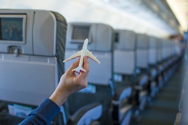 Cerrar una mano sosteniendo un modelo de avión dentro de un avión grande Foto Premium