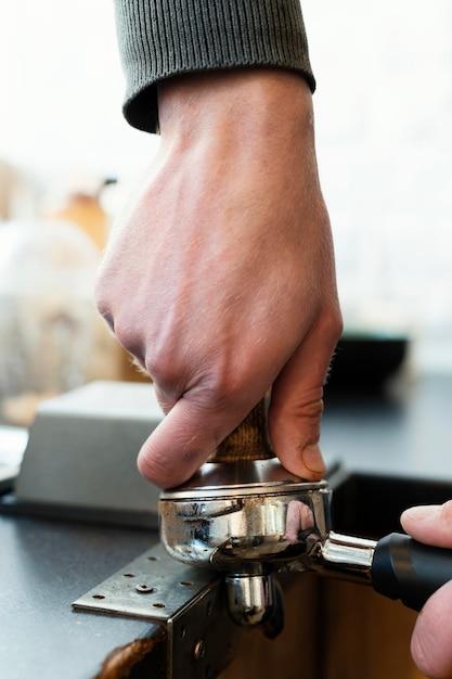 Cerrar las manos sosteniendo el artículo para hacer café Foto gratis