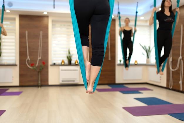 Cerrar las piernas de la mujer permanecer en la hamaca haciendo ejercicios de estiramiento fly yoga en el gimnasio Foto Premium
