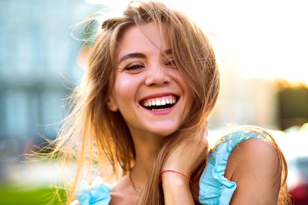 Cerrar soleado retrato de hermosa mujer magnífica con maquillaje natural y gran sonrisa asombrosa mirando a cámara, luz solar brillante, estado de ánimo positivo. Foto gratis