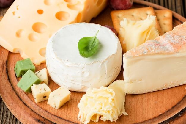 Cerrar surtido de quesos gourmet en tabla de cortar de madera Foto gratis