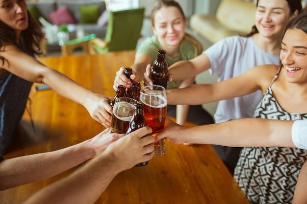 Cerrar tintineo. joven grupo de amigos bebiendo cerveza, divirtiéndose, riendo y celebrando juntos. Foto gratis