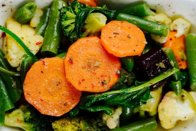 Cerrar vista superior verduras guisadas zanahorias espárragos con brócoli en un plato Foto gratis