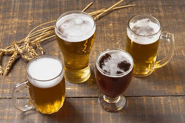 Cerveza de alto ángulo en vasos y pinta con espuma Foto gratis