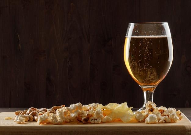 Cerveza con bocadillo en un vaso de vidrio en la mesa de madera y tabla de cortar, vista lateral. Foto gratis