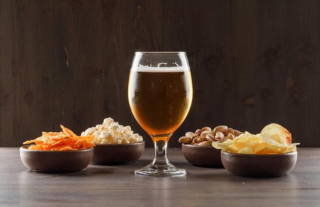 Cerveza con comida chatarra en un vaso de copa en la mesa de madera, vista lateral. Foto gratis